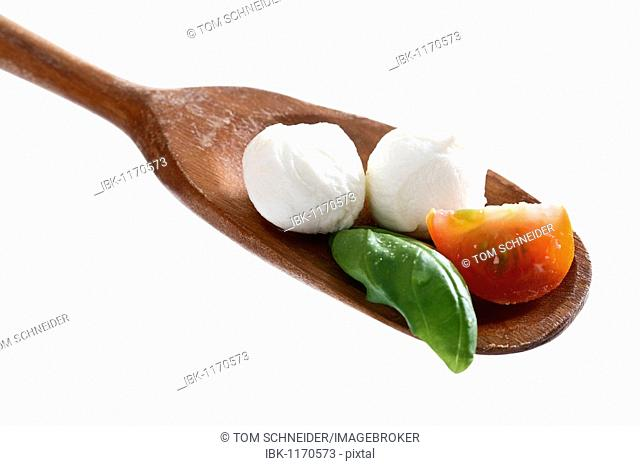 Mozzarella balls with tomato and basil on a wooden spoon