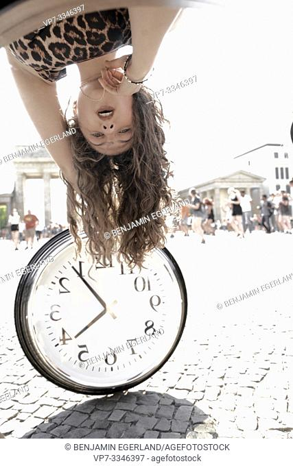 young woman upside down with time clock in front of dancing flashmob crowd next to touristic sight Brandenburg Gate, in Berlin, Germany