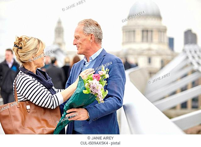 Romantic mature dating couple greeting each other on Millennium Bridge, London, UK