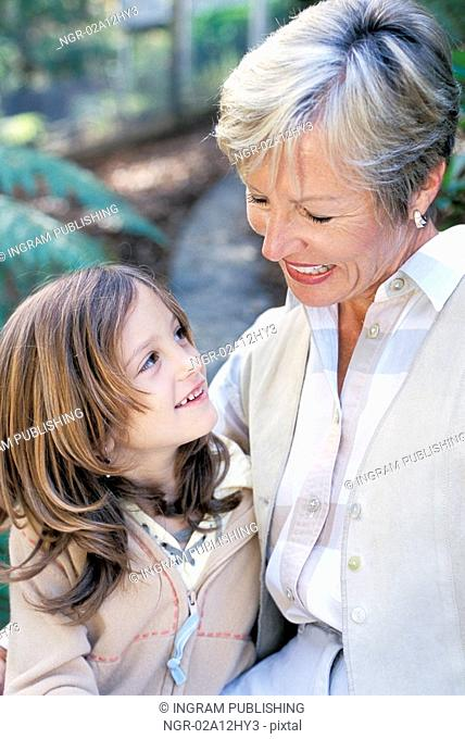 Close-up of a grandmother and her granddaughter smiling