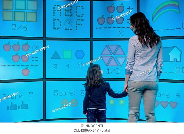 Mother and daughter standing in front of graphical screens showing educational images