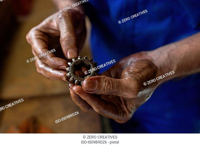 Hands of male car mechanic holding car part in repair garage