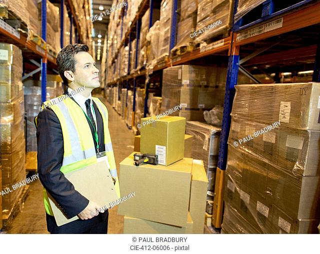 Businessman holding clipboard in warehouse