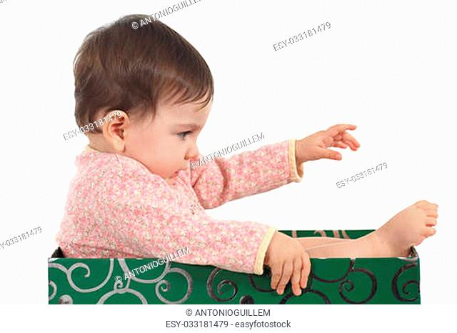 Eight months baby inside a box playing in a white background