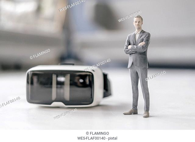 Miniature businessman figurine standing next to VR glasses