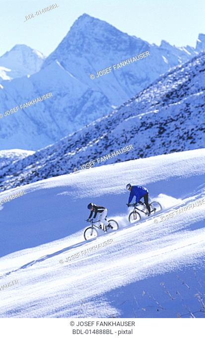two people racing down snow covered mountain on bicycles