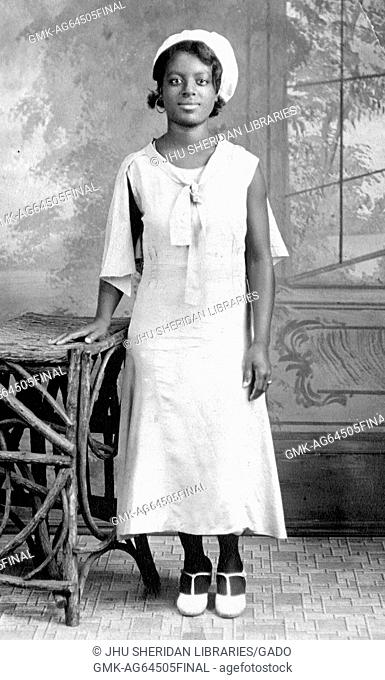Portrait of African-American young woman wearing hat and formal dress, in photographic studio, 1930