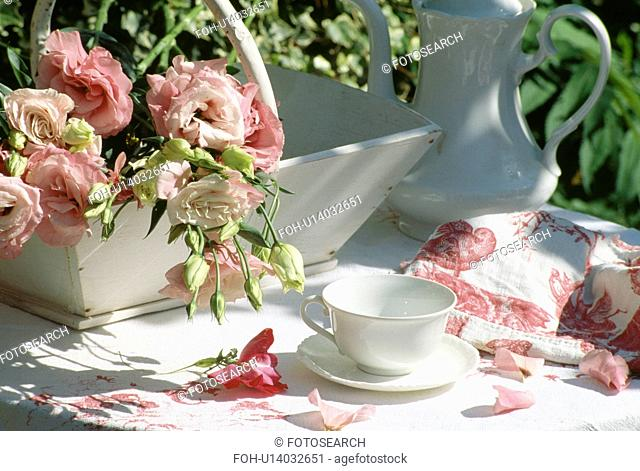 Still-life of pink roses in white trug and white coffeepot on table with rose-patterned cloth