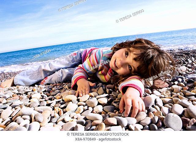 baby girl lying on the beach