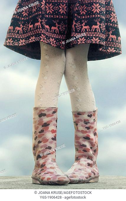 a girl in wellies on a table