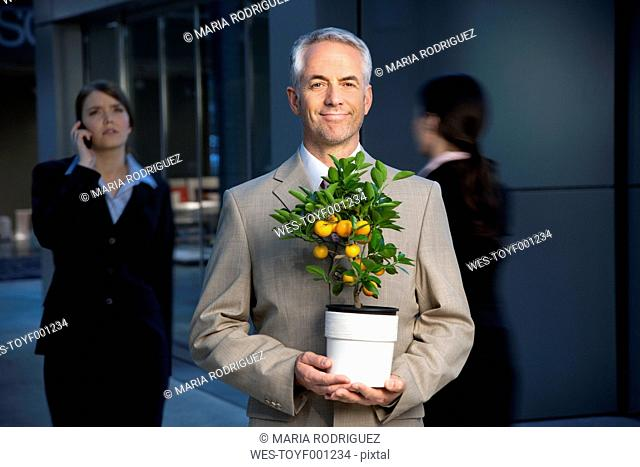 Smiling businessman holding tangerine tree with businesswoman in background