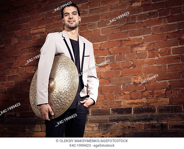 Artistic portrait of a smiling young man musicial holding a ride cymbal standing at a brick wall