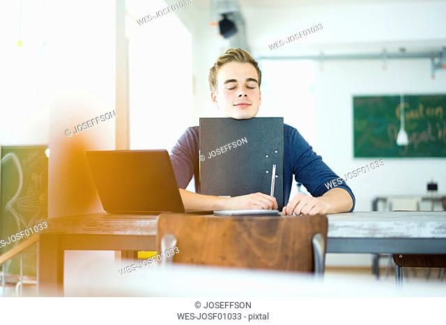 Portrait of student with laptop and file in a coffee shop