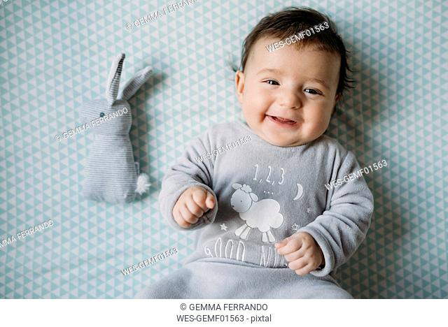 Portrait of smiling baby girl lying on bed beside toy bunny