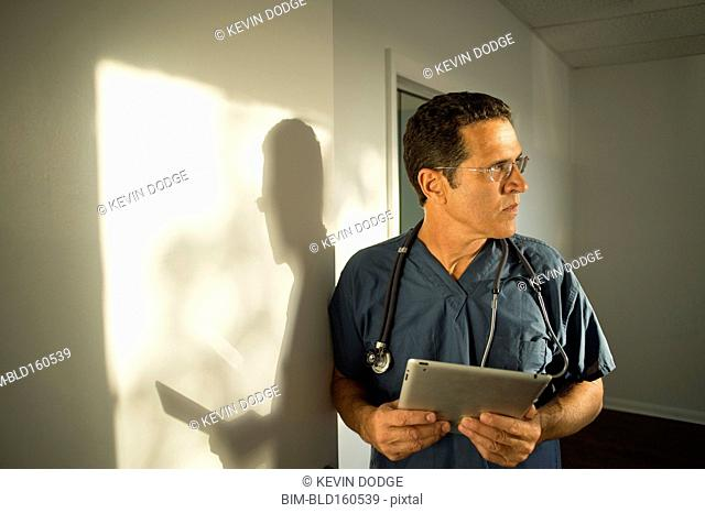 Hispanic doctor leaning on wall using digital tablet