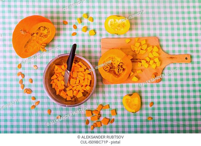 Pumpkin cut into pieces on chopping board with bowl full of cubed pumpkin, overhead view