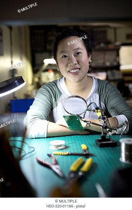 Portrait confident female electronics engineer assembling electronic components in workshop