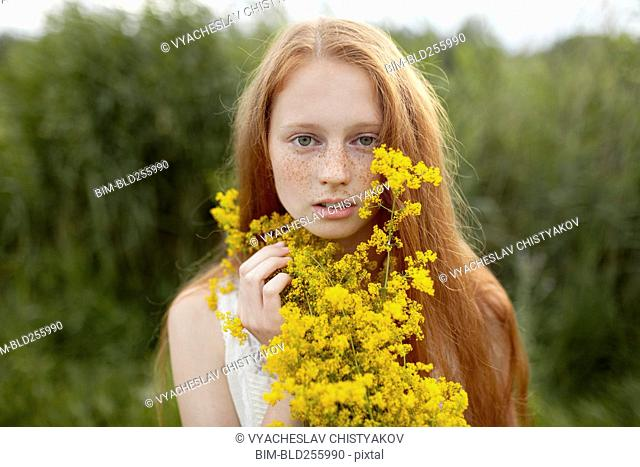 Portrait of serious Caucasian girl with freckles holding wildflowers