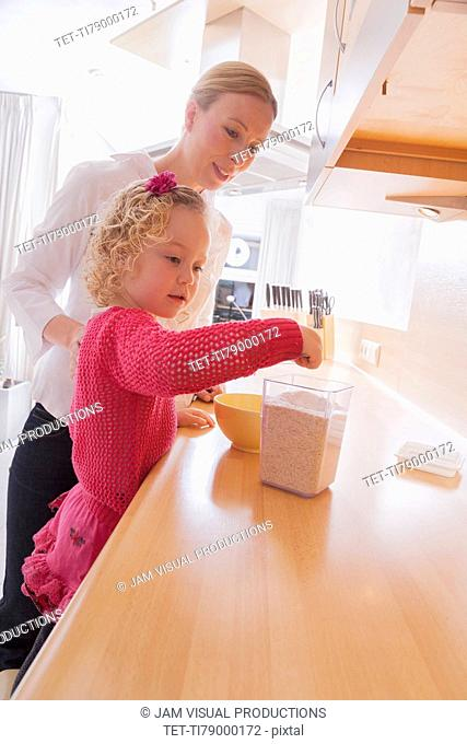 Mother watching daughter (4-5) taking out porridge from container