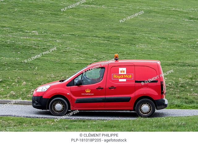 Postman driving red Peugeot Partner Royal Mail post van along desolate road in Shetland, Scotland, UK