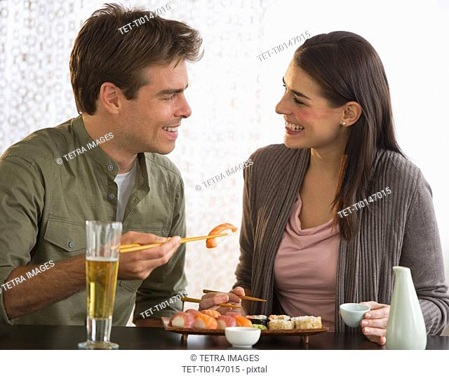 Young couple eating sushi