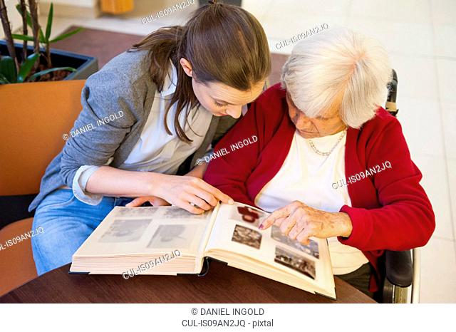 Mid adult woman and her grandmother pointing and looking at photograph album