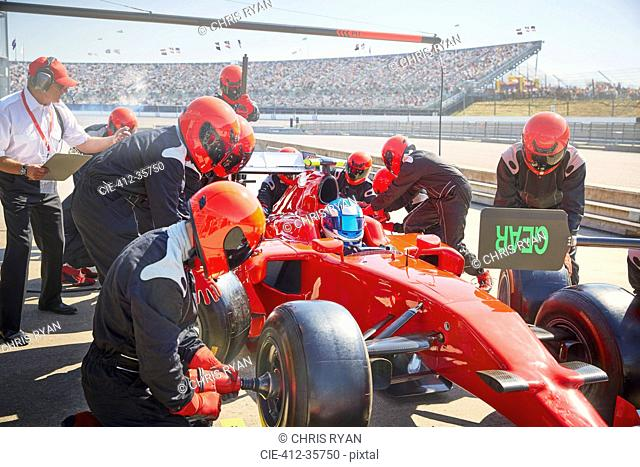 Pit crew replacing tires on formula one race car in pit lane practice session