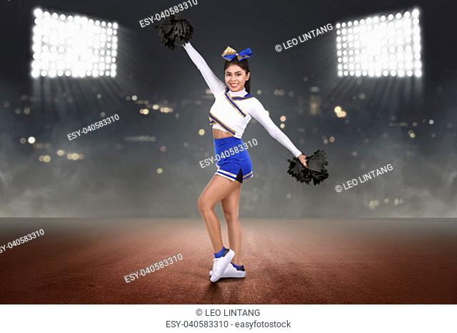 Happy asian cheerleader performing with poms on the stadium