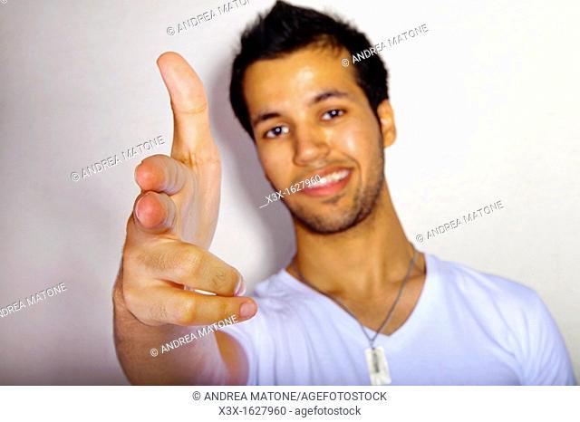 Male portrait holding hand like a gun
