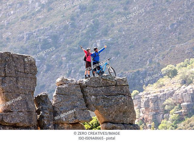 Mountain biking couple celebrating on rock formation