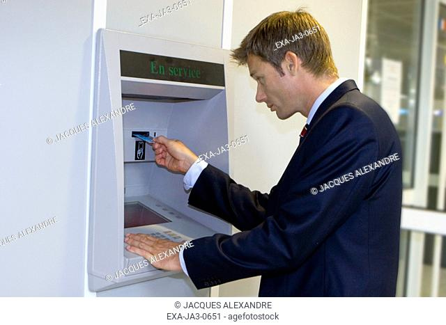 Man using automatic teller machine