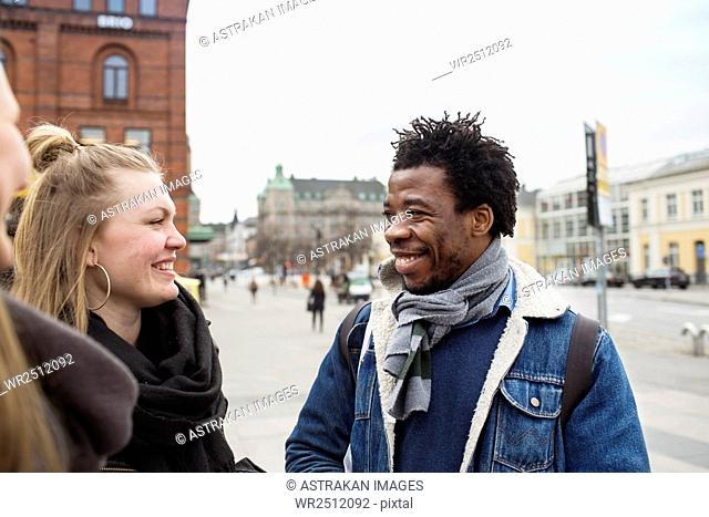 Smiling friends talking while standing in city against clear sky