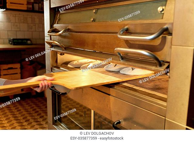 food, cooking and baking concept - baker hand with peel putting yeast dough into bread oven at bakery kitchen