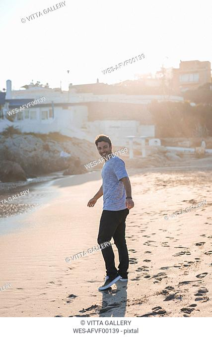 Happy young man strolling on the beach at sunset