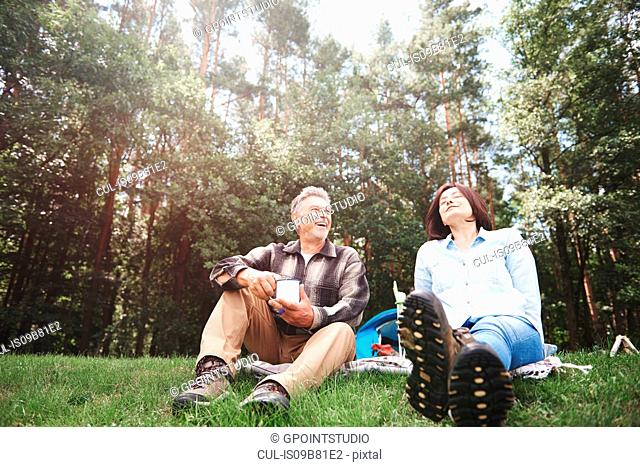 Mature couple relaxing on grass beside tent
