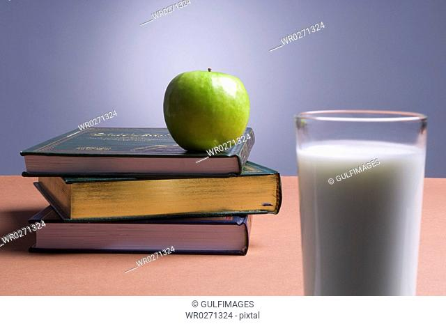 Apple on top of books, close-up