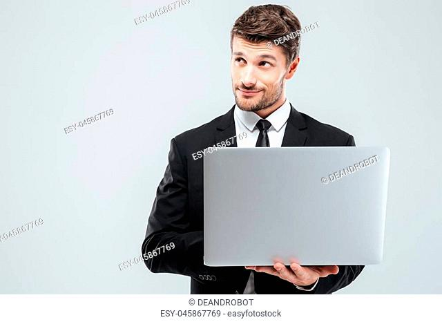 Thoughtful young businessman using laptop and thinking over white background