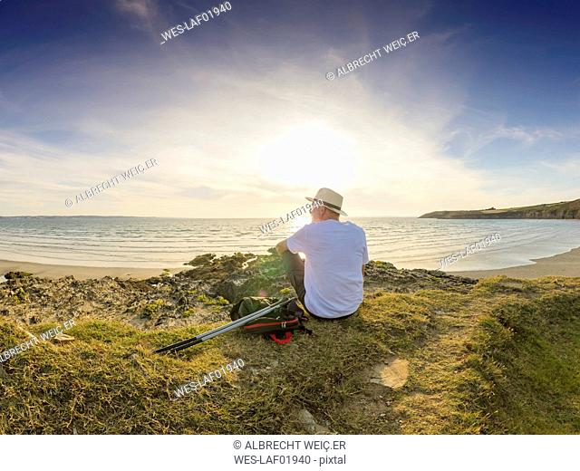 France, Bretagne, Senior man taking a break on the beach, sitting on a dune