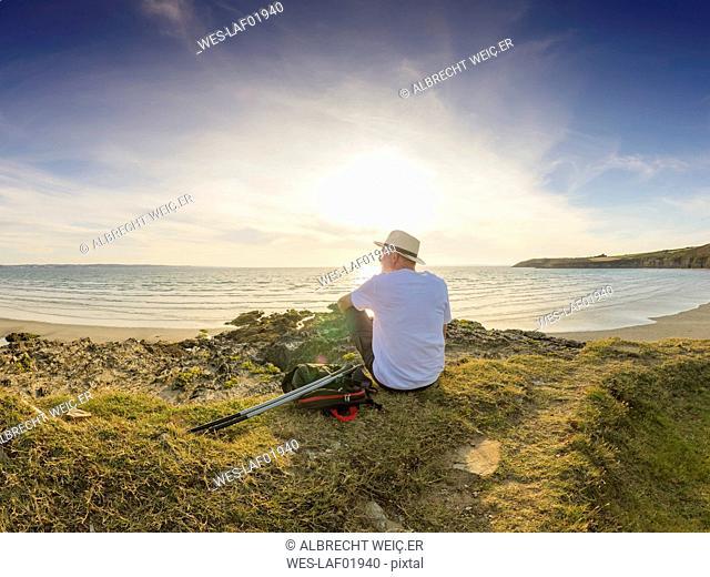 France, Bretagne, Senior man taking a break on the beach, sitting on a dune