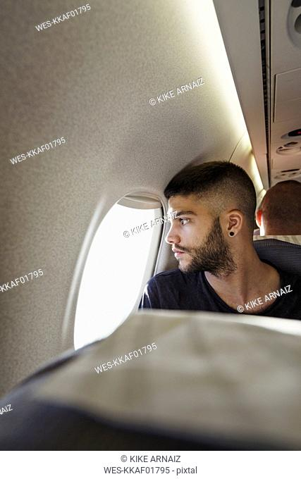 Young man in a plane looking out of window
