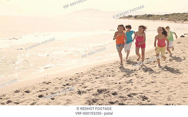 Five children running towards camera on beach