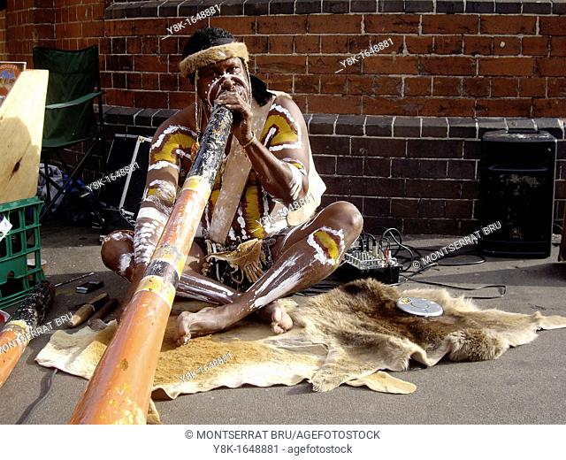 Australian Aboriginal man playing didgeridoo, body painted ocher and white, in Sydney, Australia
