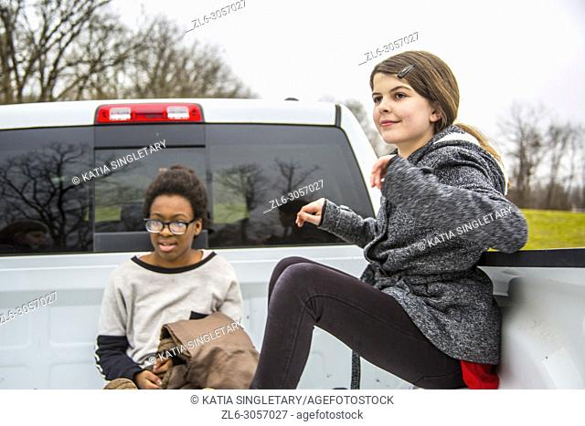 Two teens/ Pre-teens having fun in the back of a pick up truck. They are outdoor and sitting inside the truck. . One African American teen girl