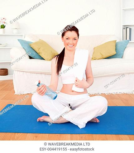 Smiling female having a rest after stretching while sitting on a