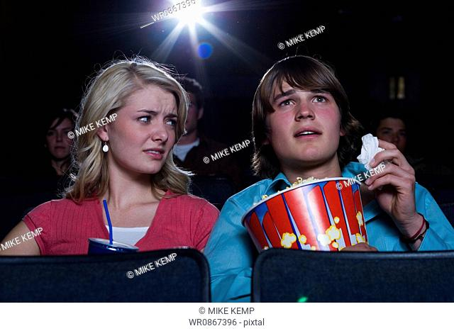 Boy with tissues crying at movie theater with girl watching