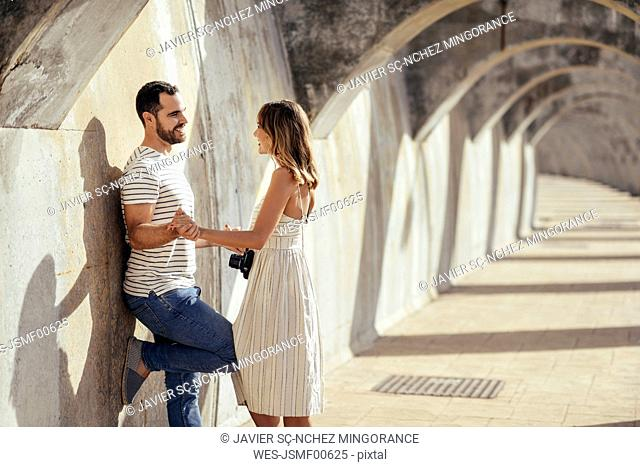 Spain, Andalusia, Malaga, happy affectionate tourist couple under an archway in the city