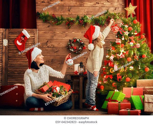 Merry Christmas and Happy Holidays! Mom and daughter decorate the Christmas tree in room. Loving family indoors