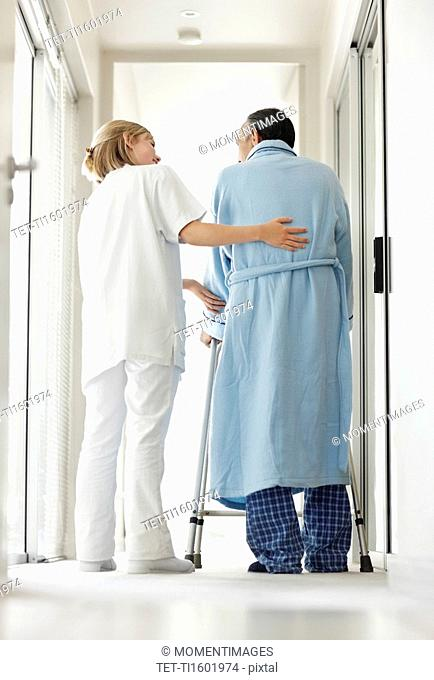 Nurse assisting patient with a walker