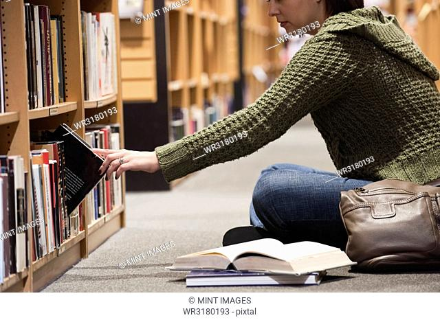 Caucasian female browsing through books in a bookstore, while sitting on the floor in front of a rack of books