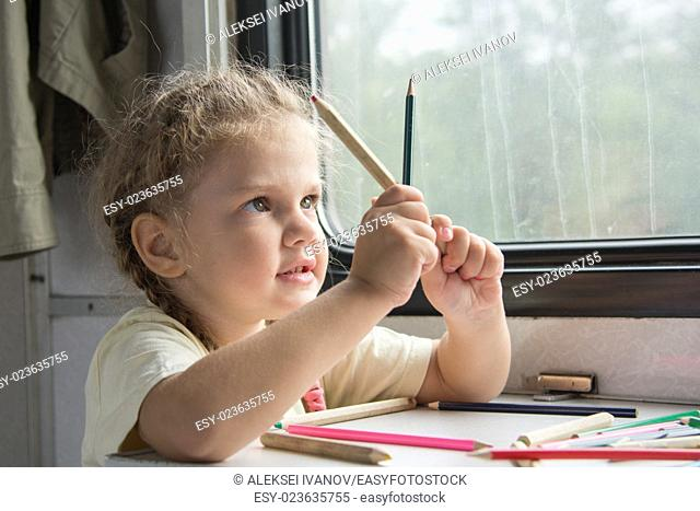 Four-year girl draws pencil in a notebook for a side table in the second-class train carriage
